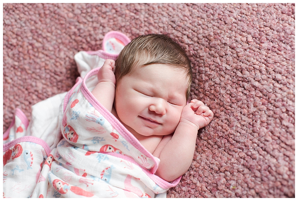 Newborn baby with headful of hair smling. Bellingham newborn photographer.