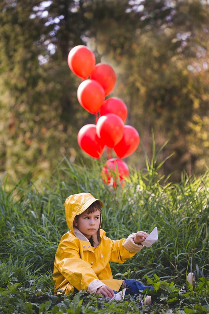 Boy dresses at Georgie from It in this It-Inspired photoshoot.  DIY It halloween costume.