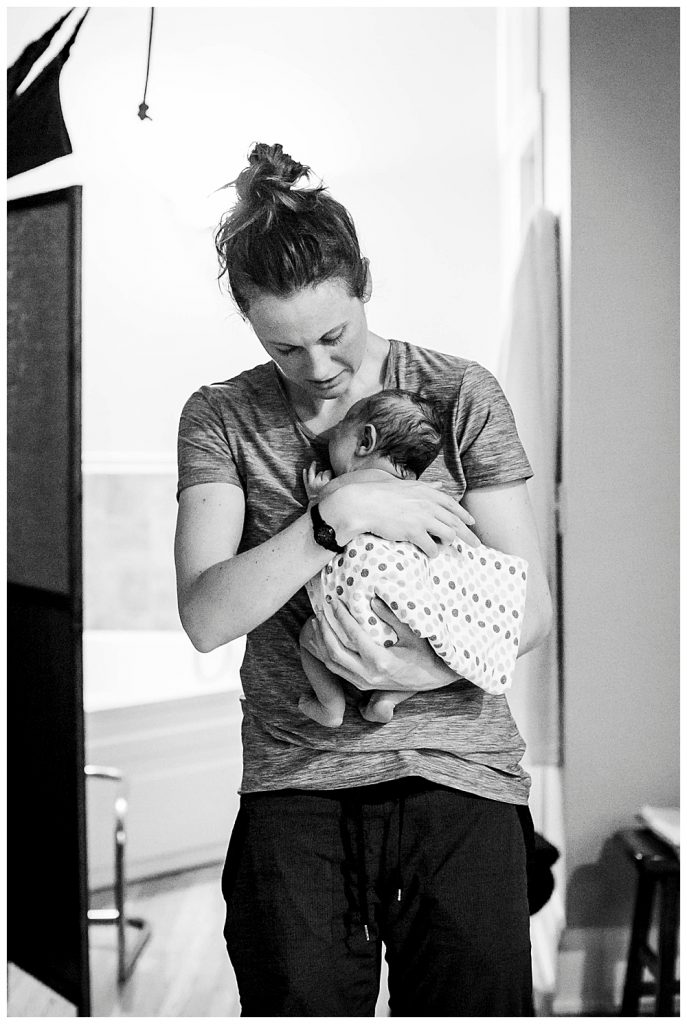 Bellingham midwife, Allie Watkins of Haven Midwifery, examines newborn after her birth.