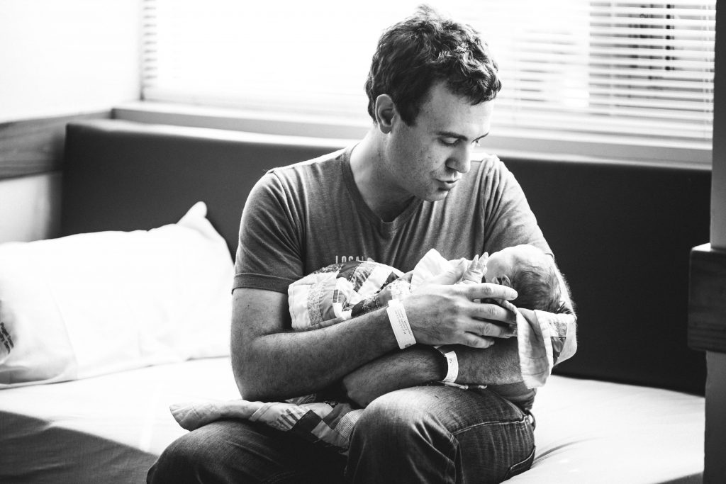 Dad cradling his newborn baby in hospital.