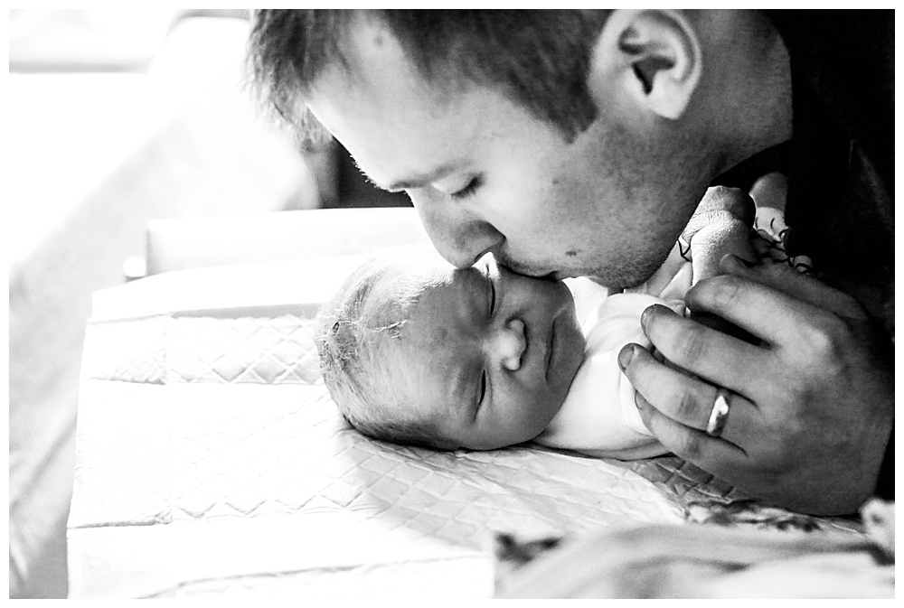 New daddy kissing her newborn baby in hospital.