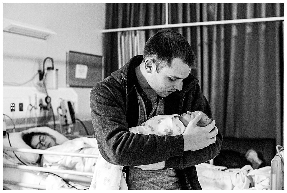Dad cuddles newborn baby while wife looks on. Belllngham birth photography by Renee Bergeron.