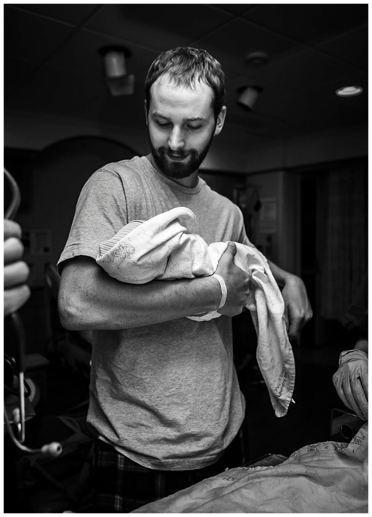 Dad holding baby after birth. Little Earthling Photography.