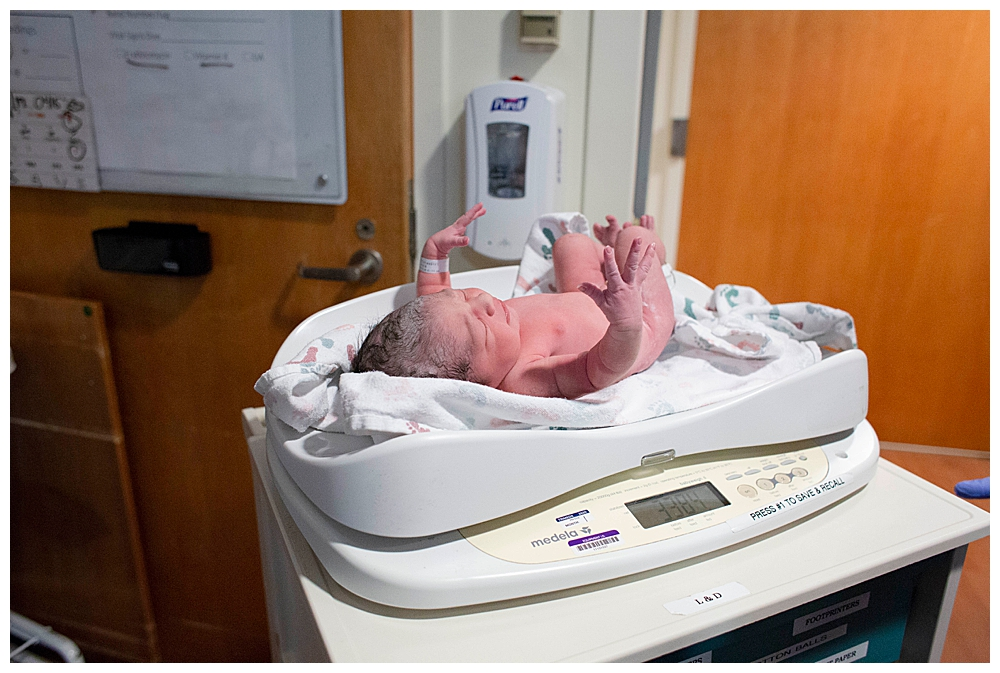 Pink baby being weighed in hospital.