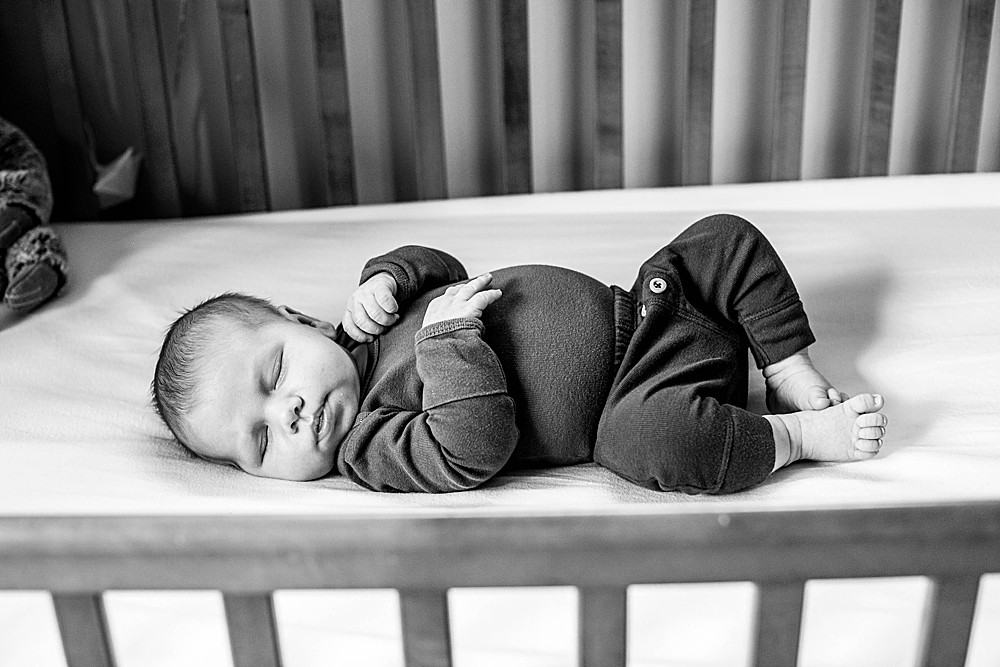 Black and white portrait of baby in crib. Bellingham photographer.