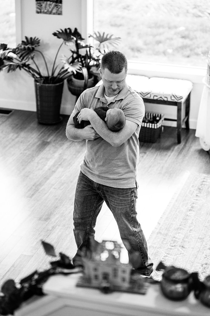 Dad walking with newborn baby. In-home portrait sessions mean I get get to capture life naturally. Bellingham lifestyle photographer.