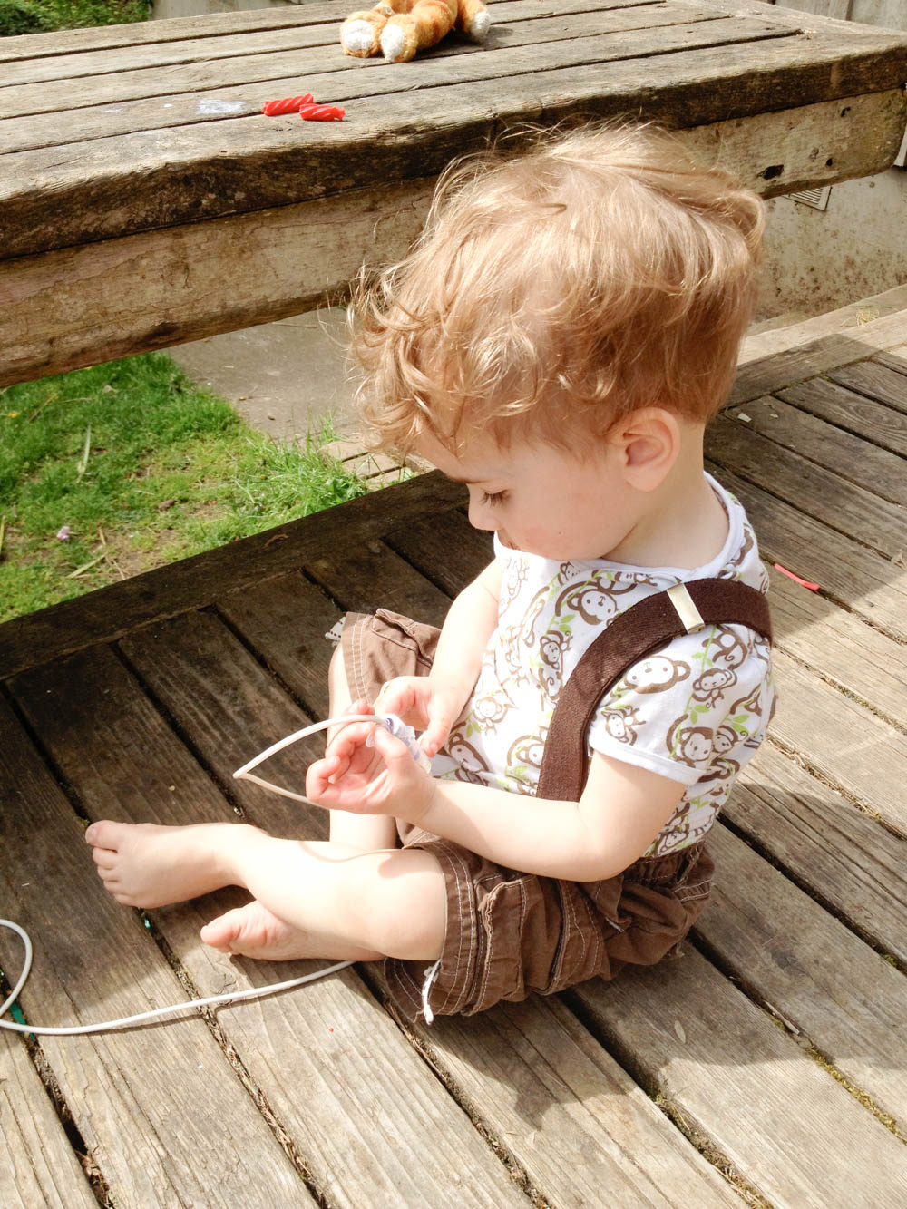 Toddler with g-tube plays outdoors on deck.