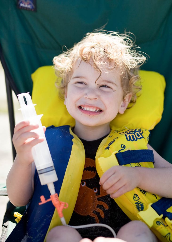 Toddler in life jacket being fed through g-tube.