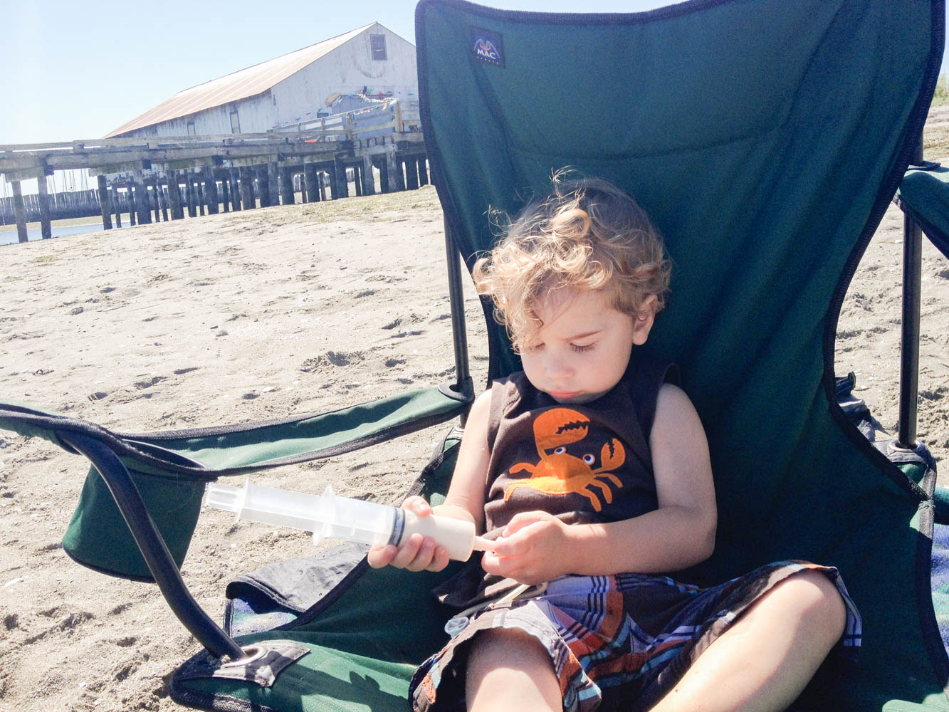 Curly haired toddler being fed through g-tube on beach.