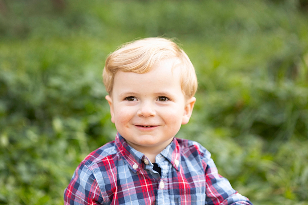 Blonde toddler smiling at camera during family photography session.