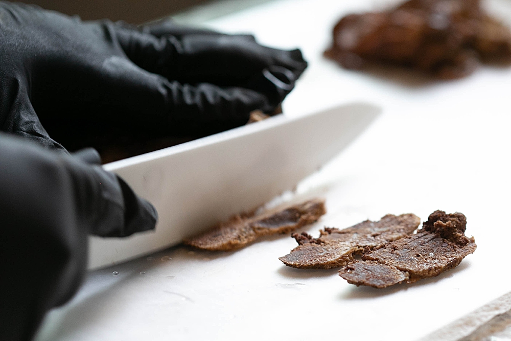 The steamed placenta is sliced thinly before being dehydrated.