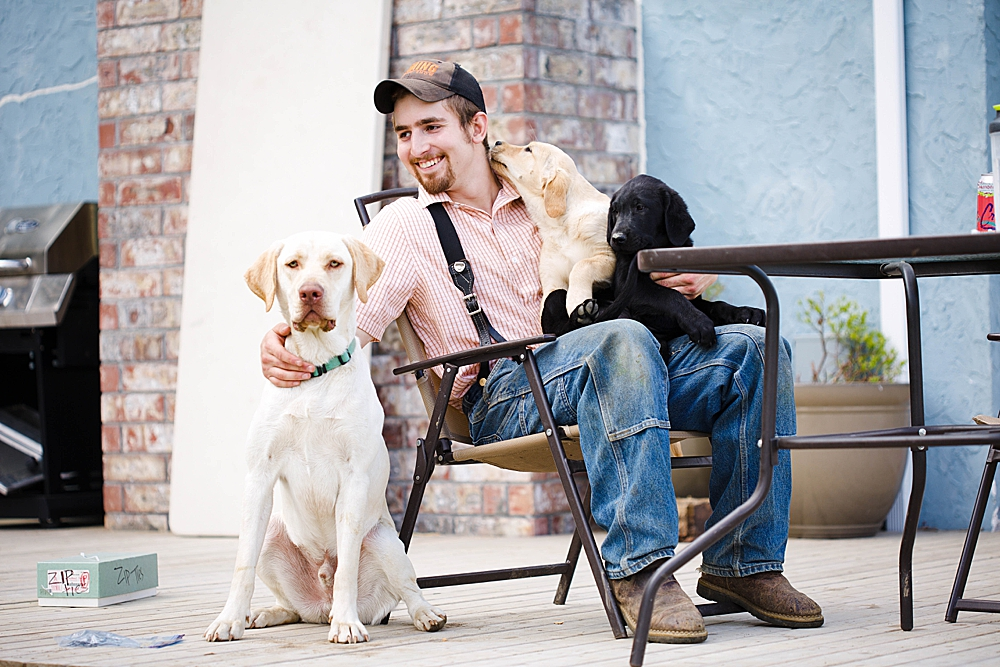 Young man in suspenders holding his dogs. Little Earthling Photography.