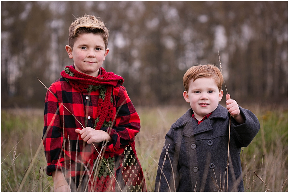 Two boys in a hay field.