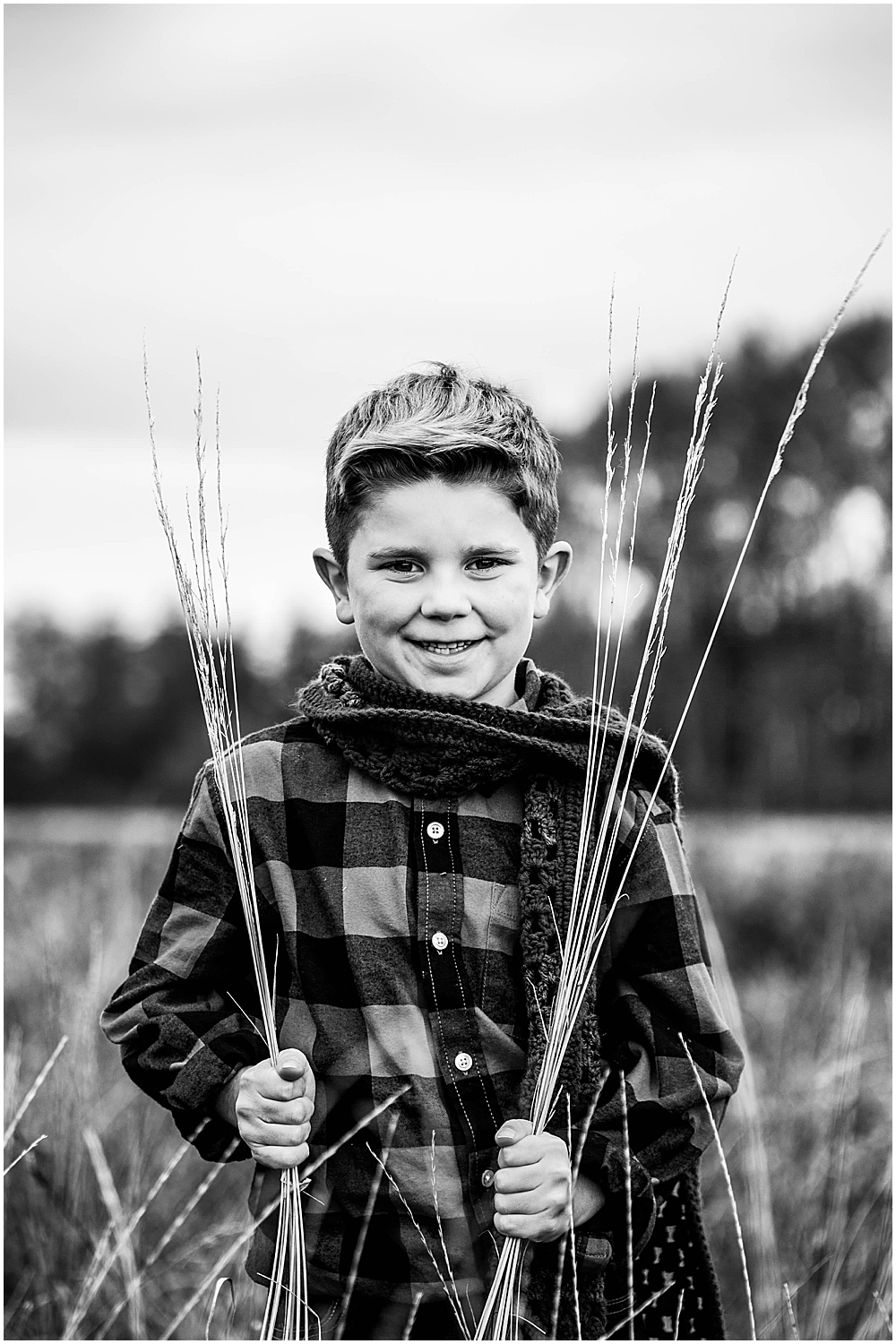 Black and white image of boy smiling in hayfield at Hovander.