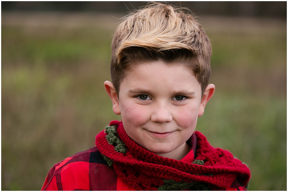 Boy in scarf smiling in hayfield.