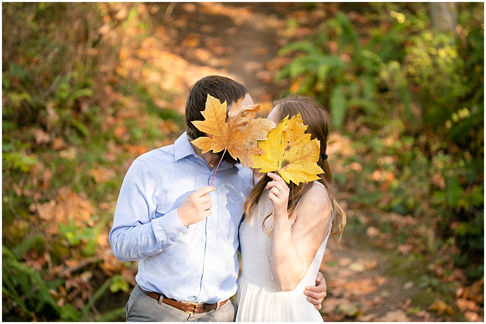 Couple covering their face with leaves as they kiss.