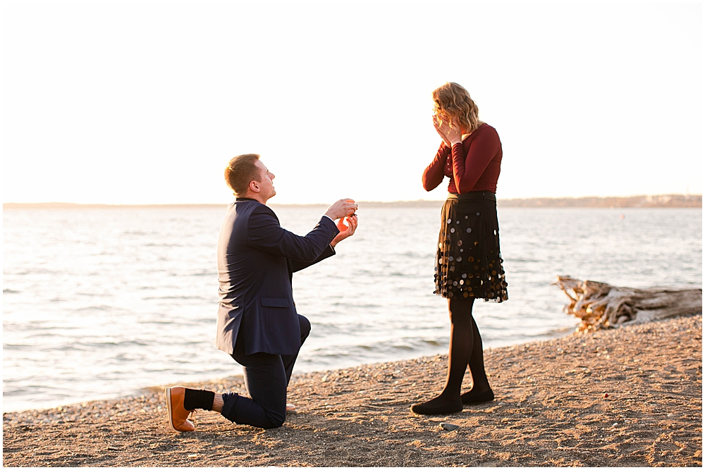 Man in a suit proposes to his girlfriend on a beach. Bellingham engagement.