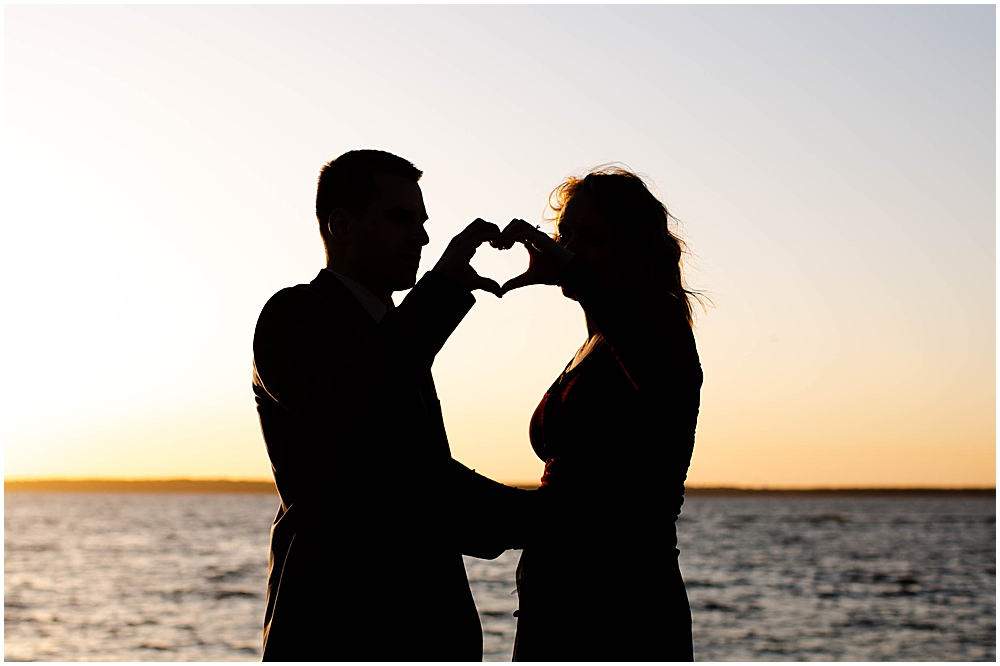 Couple at sunset making heart with their hands.