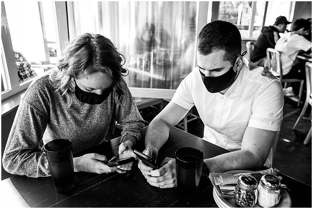 Couple wearing masks in resturant while staring at their phones