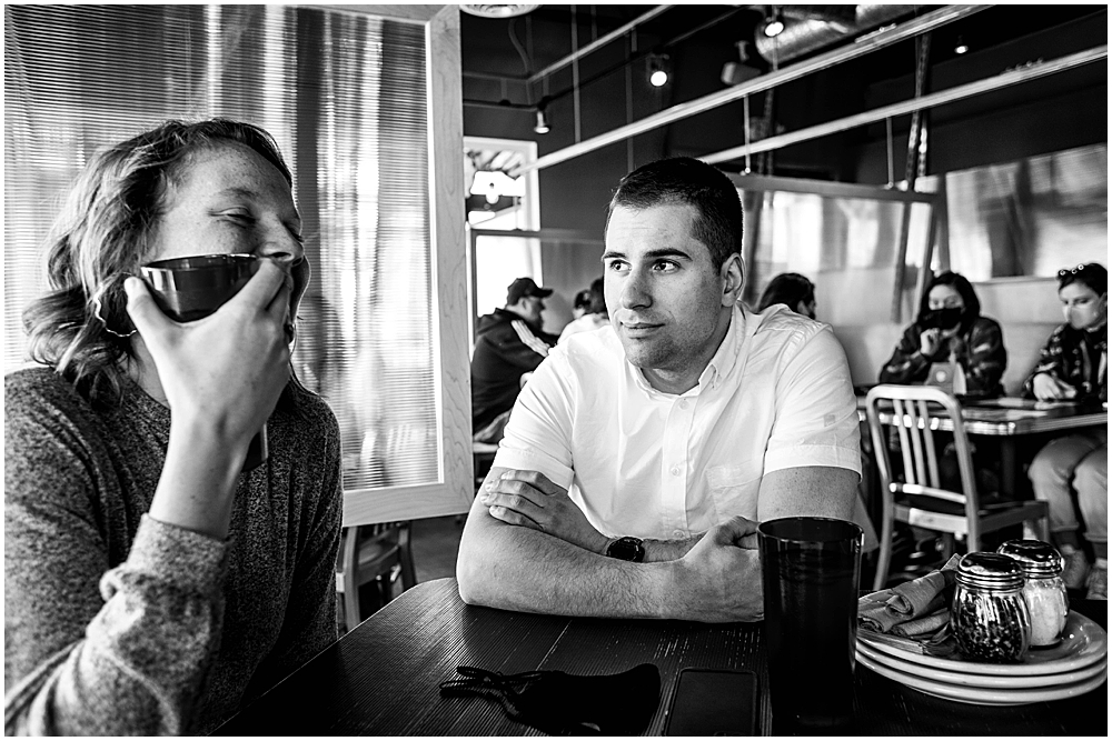 couple with masks in resturant eating pizza