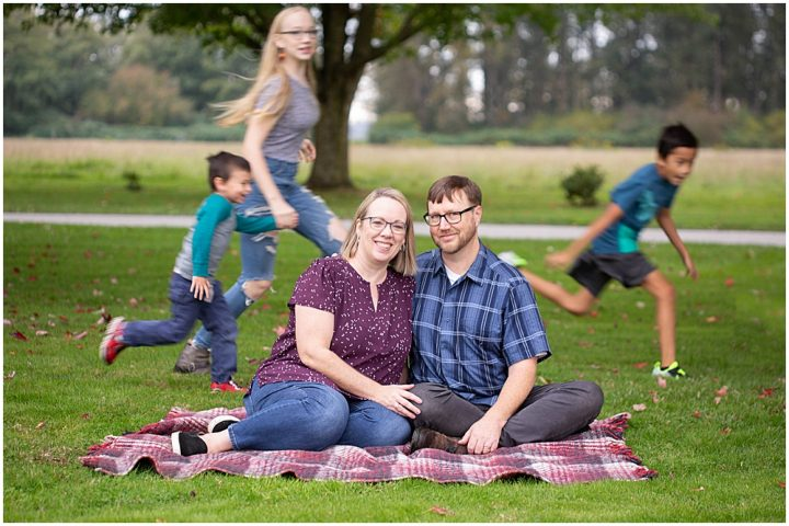 Funny family photo with kids running around behind parents. Bellingham family photographer, Renee Bergeron.